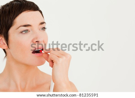 Close up of a woman taking a pill against a white background
