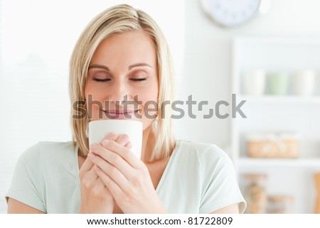 Close up of a woman taking in smell of coffee with her eyes closed in the kitchen