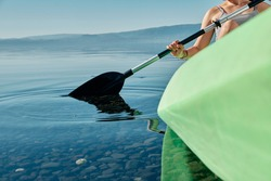 Close-up of a woman using the paddles of a kayak at the edge of a lake