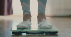 Close-up of a woman weighing herself on a scale at home. Close-up of a woman's feet on a scale.