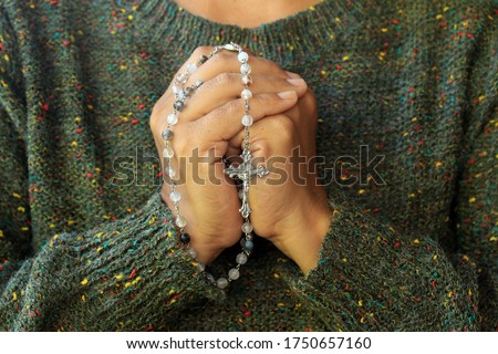 Close up of a woman with prayer hands folded to the chest holding a Rosary beads. Building deeper relationship with through praying The Rosary everyday concept. Stock photo ©