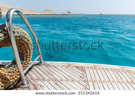 Close-up of a wooden deck end of a yacht and island on background #251342614