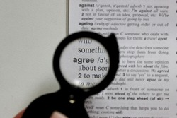 Close up of a word agree through the loupe, definition of word agree in a dictionary in a magnifying glass