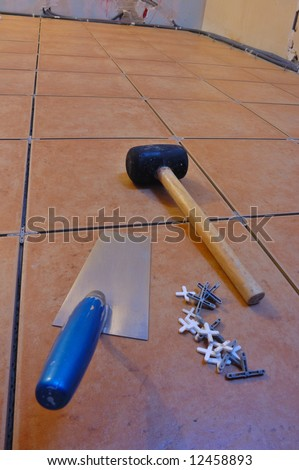 Close up of a workman's tools on a floor that is being tiled. More work in progress visible in background.