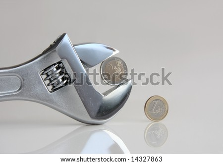 Close up of a wrench key with euro coins