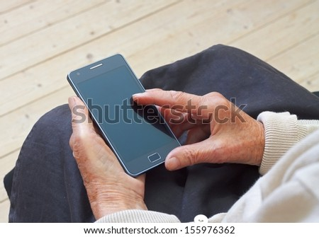 Close up of a wrinkled finger touching a mobilephone #155976362