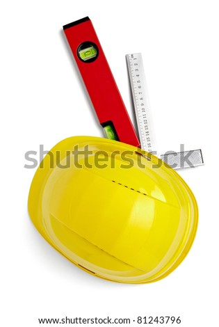 close up of  a yellow construction helmet, ruler and level on white background with clipping path - stock photo