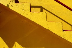 Close up of a yellow life guard tower with zigzag stairs with sunlight during summer on a beach