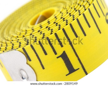 Close-up of a yellow measuring tape over white.