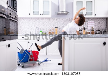 Close-up Of A Young African Woman Slipping While Mopping Floor In The Kitchen #1303107055