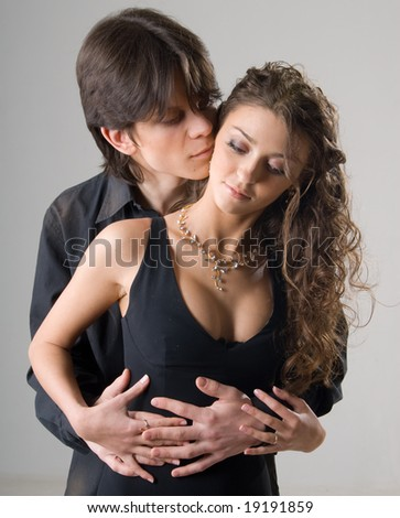 close-up of a young amorous hugging couple on grey background