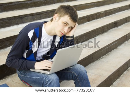 Close-up of a young attractive student on campus sits on a ladder with a laptop. Suffers from headaches