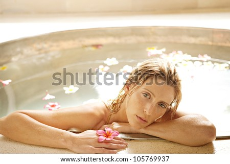 Close up of a young attractive woman in a bath of flowers, relaxing.