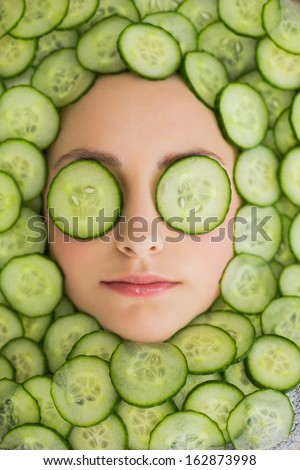 Close up of a young beautiful woman with facial mask of cucumber slices on her face at spa salon