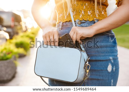 Close up of a young blonde girl using mobile phone while standing outdoors, putting mobile phone in her purse ストックフォト ©