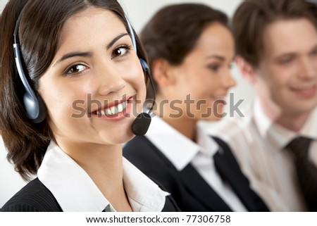 Close-up of a young businesswoman in headset looking at camera and smiling