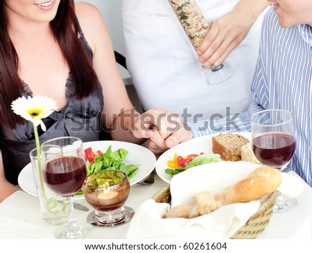 Close-up of a young couple dining at the restaurant with waiter putting pepper in their plate