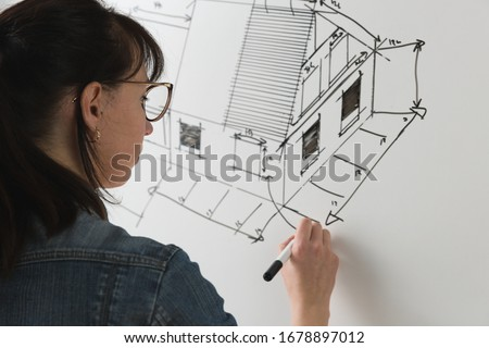 Close-up of a young female architect drawing a sketch for a new famaly home project. Concept of work on technical drawings Stockfoto ©