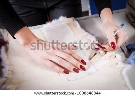 Close-up of a young furrier woman, a seamstress cuts out a piece of white natural fur #1008648844