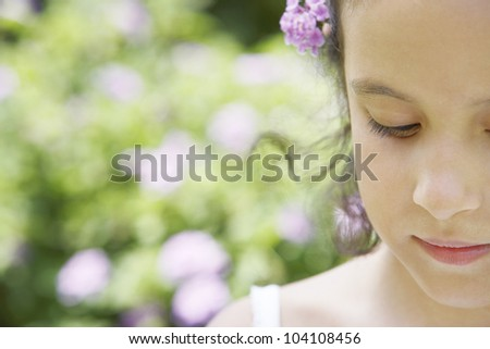 Close up of a young girl in the park, wearing a purple flower in her hair, smiling.