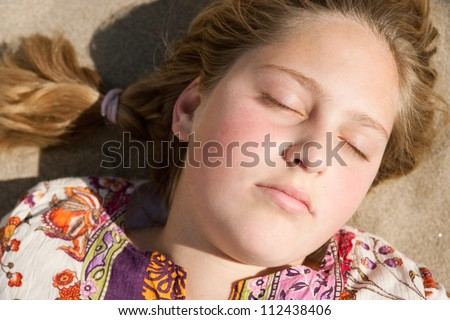 Close up of a young girl laying down on a golden sand beach, relaxing.