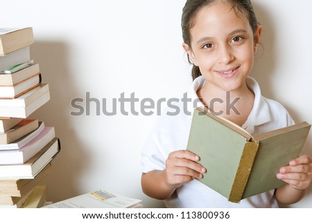 Close up of a young girl reading a book at home, sitting next to a pile of books.
