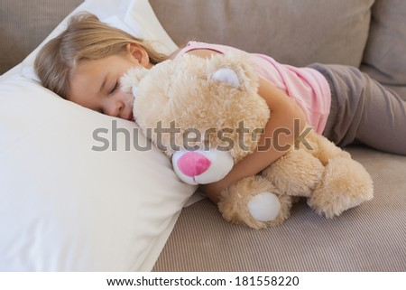 Close-up of a young girl sleeping on sofa with stuffed toy in the living room at home