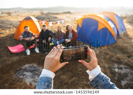 Close up of a young girl taking a picture with mobile phone of her friends sitting at the tent outdoors