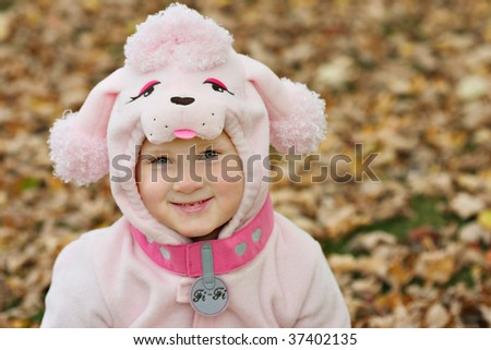 close up of a young girl wearing a pink poodle costume