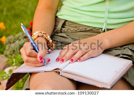 Close-up of a young girl writing into her diary, in the park
