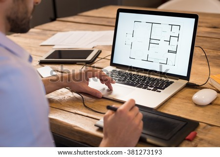 Close up of a young interior designer working in office. Architect working on laptop at new house project with graphics tablet. Interior designer studying layout of his house project on computer.
