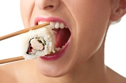 Close-up of a young lady eating a sushi roll