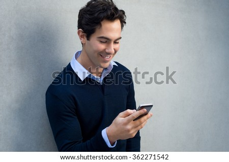 Close up of a young man leaning against a grey wall using mobile phone. Portrait of a happy business man holding a smartphone. Man in casual typing and reading a message on cell phone with copyspace.  #362271542
