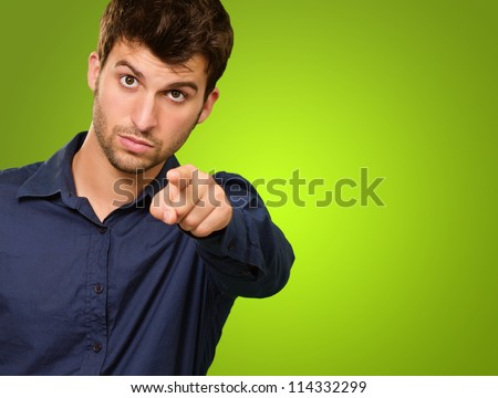 Close-up Of A Young Man Pointing On Green Background
