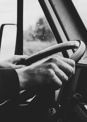 Close-up of a young man's hands holding the steering wheel of an old vintage retro style bus. Black and white image.