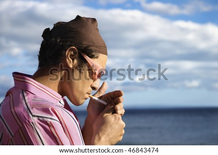 Close-up of a young man standing by the ocean and lighting a cigarette. Horizontal shot.