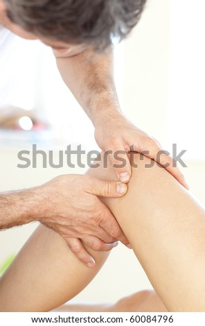 Close-up of a young physical therapist giving a leg massage in a health center