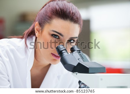 Close up of a young scientist posing with a microscope in a laboratory
