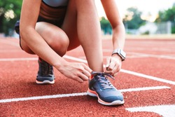 Close up of a young sportsgirl tying her shoelaces at the stadium