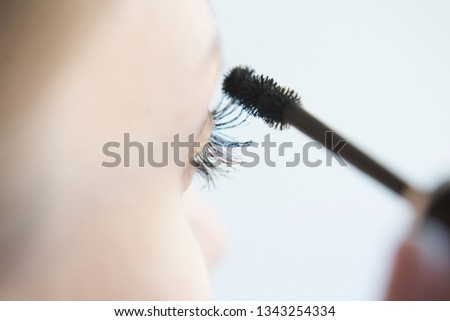 Close up of a young woman applying mascara on a white background. Make-up And Cosmetics Concept. Long Black Thick Eyelashes Applying Mascara With Cosmetic Brush.