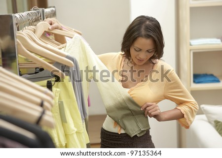 Close up of a young woman examining garments in fashion clothes.