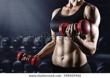 Close-up of a young woman exercising with weights in the gym