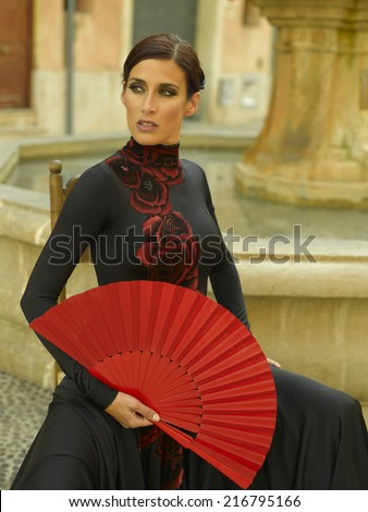 Close-up of a young woman holding a fan
