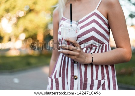 Close-up of a young woman in a summer pink striped dress with a milkshake in a sunny day outdoors in the park. Stylish girl enjoys a walk and a sweet drink outdoors in the park. #1424710496