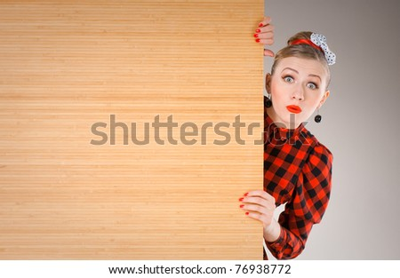 Close-up of a young woman looks out for the billboard. place text on wooden background that looks out for this young woman with a surprised face