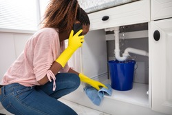 Close-up Of A Young Woman Placing Blue Bucket Under Water Leaking From Sink Pipe
