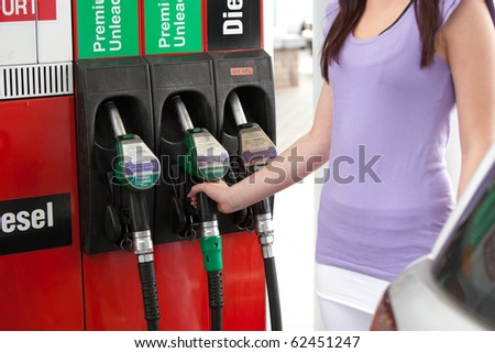 Close-up of a young woman refueling her car in a gas station