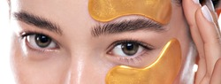 Close up of a young woman's eyes with golden eye patches. Charming caucasian model with natural make-up on white background. Natural feminine beauty, skin care and beauty concept.