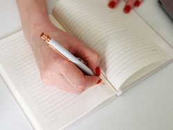 Close-up of a young woman's hands writing a plan of the day in a notebook at the workplace at the computer. The concept of working and studying at home.