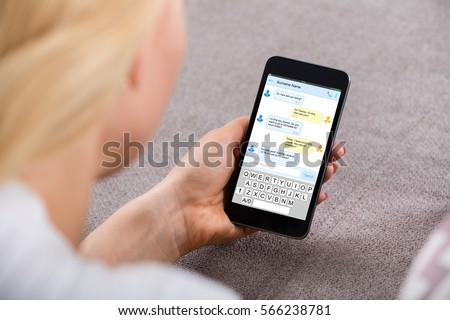 Close-up Of A Young Woman Sending Text Message Using Mobile Phone At Home